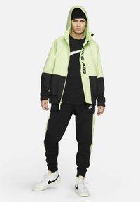 Nike Sportswear - AIR - Tracksuit bottoms - black/light liquid lime/white - 1