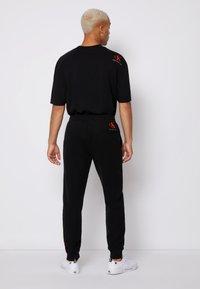 Calvin Klein Jeans - BADGE PANT - Tracksuit bottoms - black - 2