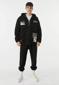 Bershka - MIT BAUCHTASCHE UND PRINT  - Veste en jean - black - 1