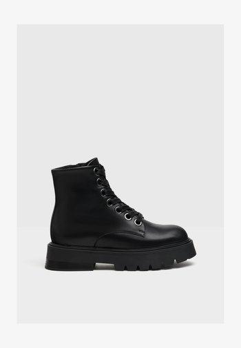 PLATEAUSTIEFELETTEN AUS LEDER - Ankle boots - black