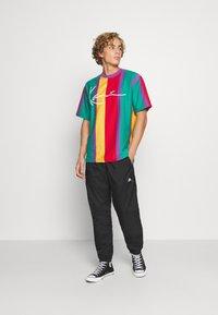 Karl Kani - SIGNATURE STRIPE TEE UNISEX - Print T-shirt - purple - 1
