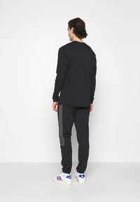 adidas Originals - Tracksuit bottoms - black - 2