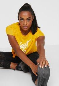 Nike Performance - DRY SIDE TIE  - T-shirt z nadrukiem - university gold/white - 3