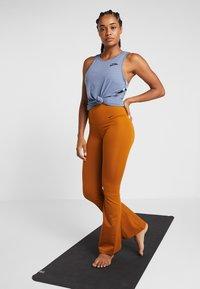 Nike Performance - STUDIO FLARE - Pantalon de survêtement - burnt sienna/black - 1