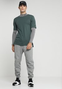 Nike Performance - THRMA TAPER - Pantalon de survêtement - dark grey heather/black - 1