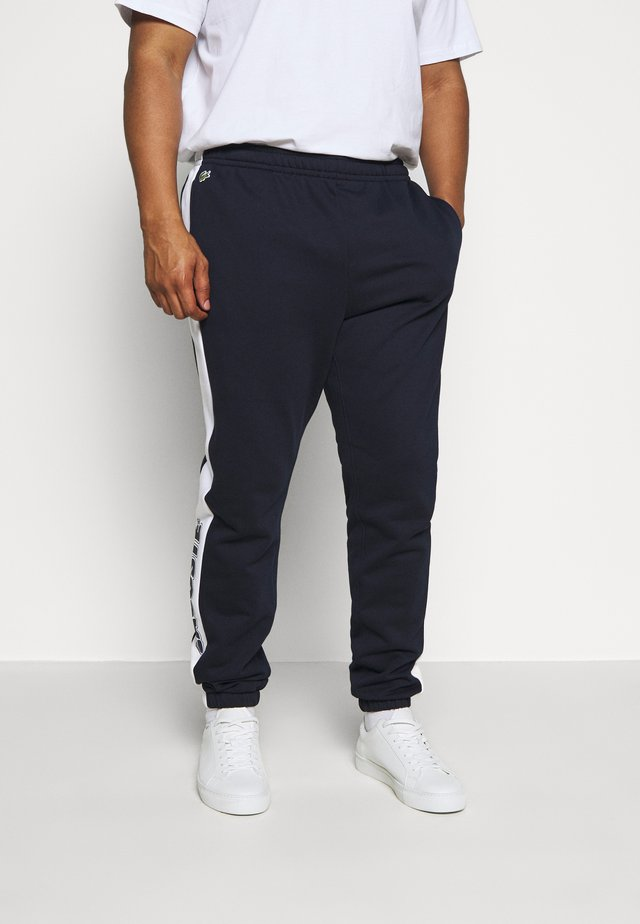 PLUS - Pantalon de survêtement - marine/blanc