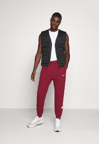Nike Sportswear - REPEAT  - Tracksuit bottoms - team red - 1