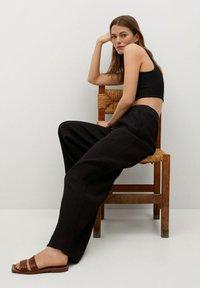 Mango - FLUIDO PLISADO - Trousers - black - 5