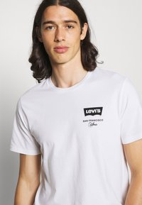 Levi's® - HOUSEMARK GRAPHIC TEE UNISEX - T-shirt imprimé - left chest batwing white - 3