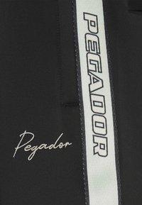 Pegador - WIDE TRACKPANTS UNISEX - Pantalon de survêtement - black/mint - 9
