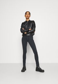 Vero Moda - VMLOVE SHORT COATED JACKET - Imitert skinnjakke - black - 1