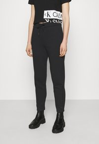 Calvin Klein Jeans - SHINY RAISED PANT - Tracksuit bottoms - black - 0