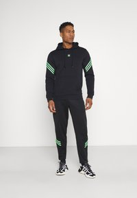 adidas Originals - TRACK PANT UNISEX - Tracksuit bottoms - black/shock lime - 1