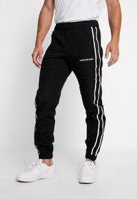 Calvin Klein Jeans - SIDE STRIPE TRACK PANT - Tracksuit bottoms - black - 0