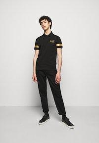 EA7 Emporio Armani - Polo shirt - black gold - 1