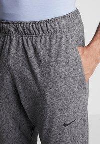 Nike Performance - M NK DRY PANT HPR DRY LT YOGA - Tracksuit bottoms - black - 3