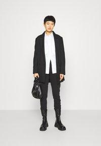 Calvin Klein Jeans - GLITTER MONOGRAM  - Tracksuit bottoms - black - 1
