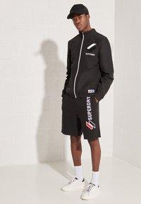 Superdry - CAGOULE - Training jacket - black - 0