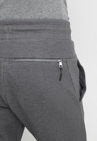 Nike Sportswear - OPTIC - Tracksuit bottoms - dark grey/heather - 5