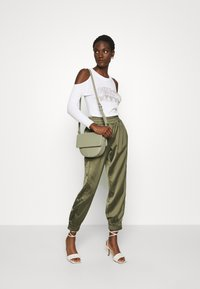 Guess - EUPHEMIA - Tracksuit bottoms - greek olive - 1