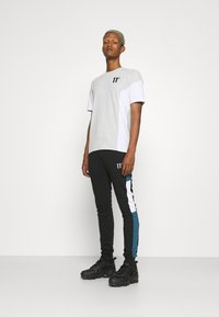 11 DEGREES - CUT AND SEW JOGGERS SKINNY FIT - Teplákové kalhoty - black/indian teal/white - 1