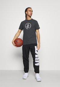 Nike Performance - STARTING PANT - Tracksuit bottoms - black/white - 1