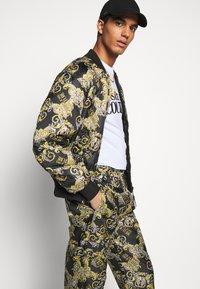 Versace Jeans Couture - RISTOP LOGO BAROQUE - Pantaloni sportivi - nero - 4