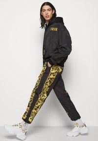 Versace Jeans Couture - PRINT BAROQUE - Tracksuit bottoms - black - 3