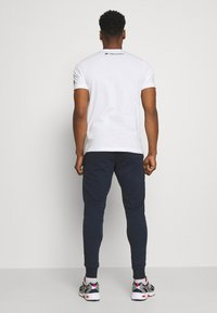 New Balance - ESSENTIAL STACK LOGO  - Tracksuit bottoms - eclipse - 2