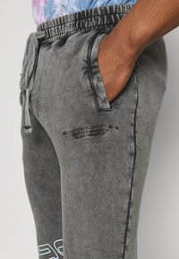 The Couture Club - COUTURE WAVE PRINT RELAXED JOGGER - Tracksuit bottoms - grey acid wash - 4