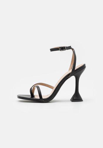 TREVIAH - T-bar sandals - black