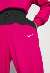 Nike Sportswear - Tracksuit bottoms - fireberry/black/white - 6