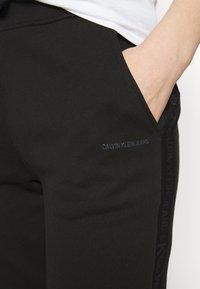 Calvin Klein Jeans - LOGO PANTS - Tracksuit bottoms - black - 4