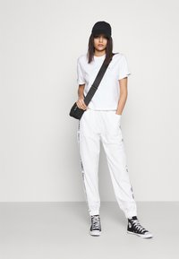 Tommy Jeans - JOGGER TAPE RELAXED - Tracksuit bottoms - white - 1