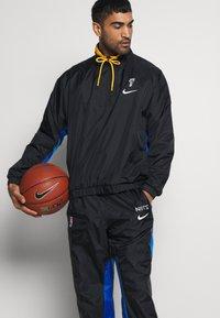 Nike Performance - NBA BROOKLYN NETS CITY EDITION TRACKSUIT - Tracksuit - black/royal blue/university gold - 5