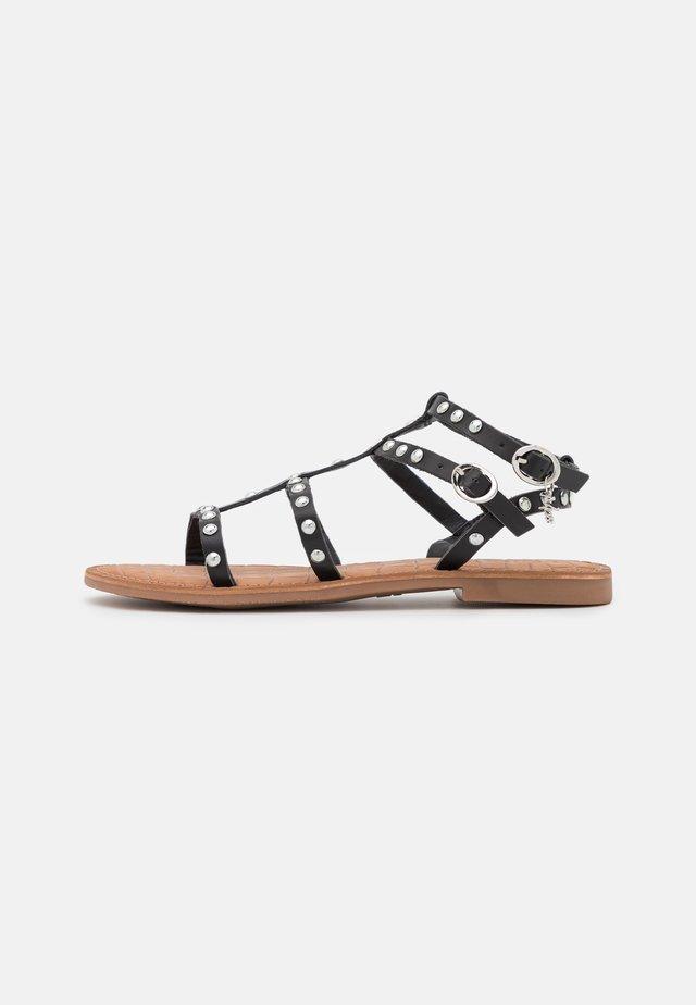 GUGAN - Sandaalit nilkkaremmillä - black