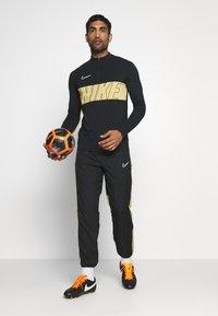 Nike Performance - DRY ACADEMY PANT - Verryttelyhousut - black/jersey gold/white - 1
