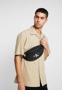 Calvin Klein Jeans - COATED ROUND STREET PACK - Bum bag - black - 1