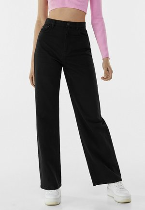 Fließende - Flared Jeans - black