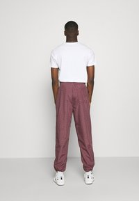 Carhartt WIP - ALISTAIR PANT - Tracksuit bottoms - black/etna red - 2