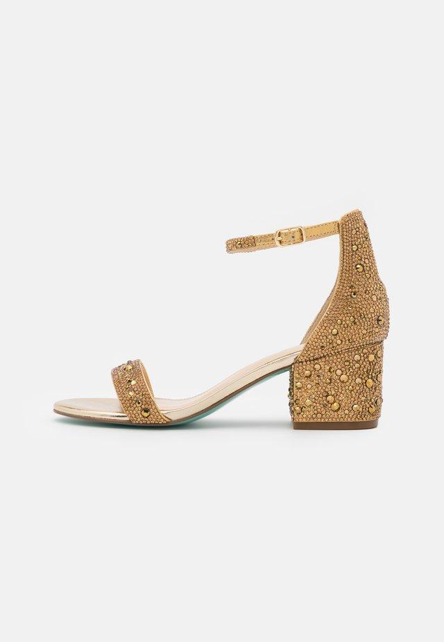 MARI - Sandaalit nilkkaremmillä - gold