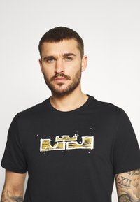 Nike Performance - DRY LOGO TEE - Print T-shirt - black/gold dart - 3