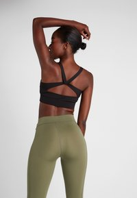 Puma - PAMELA  REIF X PUMA TWISTED BACK CROP  - Sport BH - black - 2