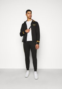 EA7 Emporio Armani - Tracksuit bottoms - black/gold - 1