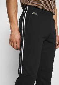 Lacoste - Tracksuit bottoms - black/white - 3