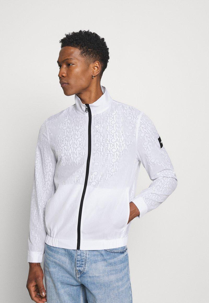 Calvin Klein - TRANSPARENT RIPSTOP LOGO BLOUSON - Summer jacket - white