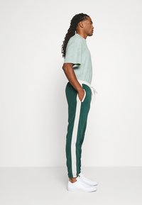 WRSTBHVR - TRACKPANTS LOUNGIN - Tracksuit bottoms - green/off white - 3