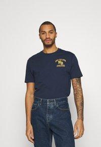 New Balance - ATHLETICS VARSITY TEE - Print T-shirt - dark blue - 0