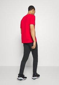 Puma - EVOSTRIPE - Pantalon de survêtement - black - 2