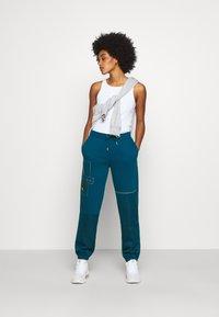 Nike Sportswear - PANT - Tracksuit bottoms - valerian blue/deep ocean/metallic gold - 1